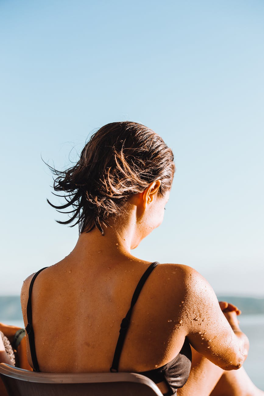 woman with short flying hair on sunny beach